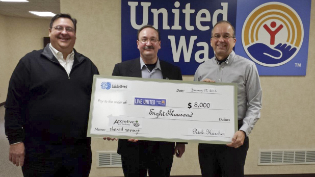 Proto of Bill Rieth accepting a check on behalf of the nonprofit United Way of Elkhart County from Rick Karcer and Mark Hatley